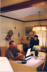 "John Baldi plays ""The Writer"" at typwriter, while Sean sets his camera up in Massapequa.  The homeowners (the late Rose & Santo Tavormina) of this location are depicted in a life-like artistic drawing that hangs on the upper middle portion of this photo."