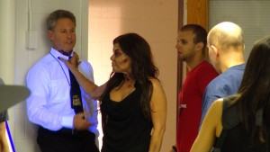 "Actor David Denowitz playing ""Captain Friedkin"" prepares to get his throat ripped out by Vala Schneider (Diana Noris) with Stunt Coordinator Matt Solazzo (in red shirt to the right) orchestrating their physical action"